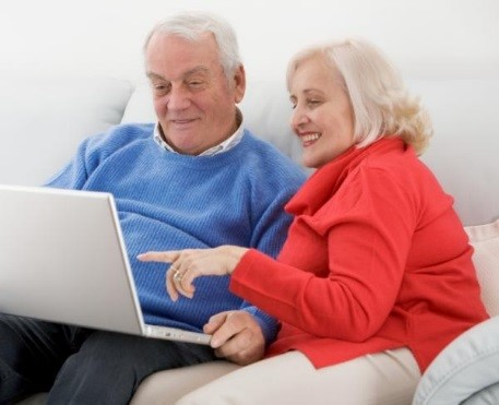 Senior couple on a couch looking at a laptop.